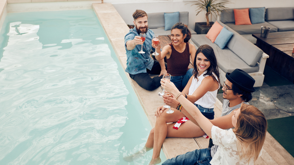 High angle shot of young people sitting by the pool having wine and smiling. Group of multiracial friends toasting at pool party outdoor.